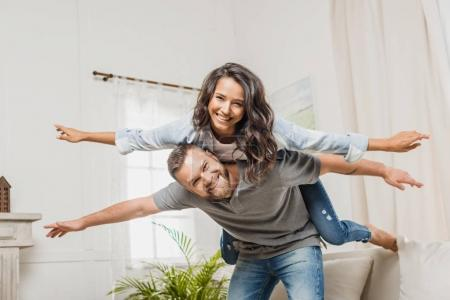 Photo for Young smiling man piggybacking his attractive girlfriend at home - Royalty Free Image