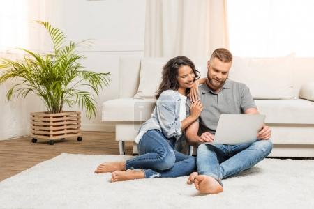 Photo for Young smiling couple using laptop while sitting on carpet at home - Royalty Free Image