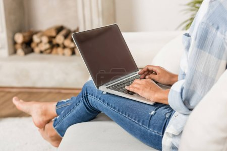 Photo for Cropped shot of young woman using laptop with blank screen while sitting on sofa at home - Royalty Free Image