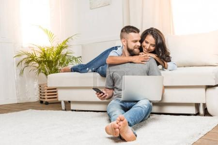 Photo for Happy young couple using laptop and smartphone while sitting together at home - Royalty Free Image