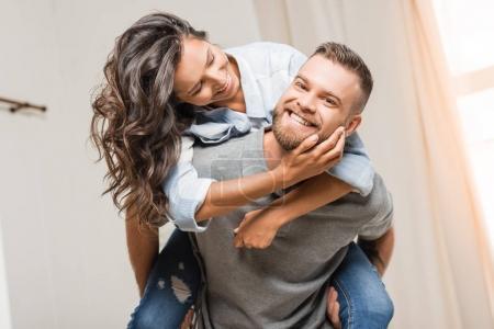 Photo pour Portrait de l'homme heureux regardant la caméra tout en tirant avec la femme à la maison - image libre de droit