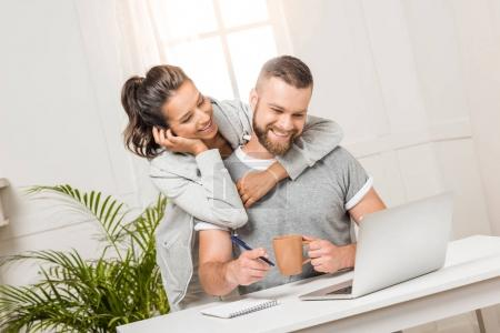Photo for Happy woman hugging man that sitting at workplace at home - Royalty Free Image