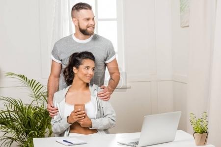Photo for Man hugging woman with cup of coffee at table with laptop at home - Royalty Free Image