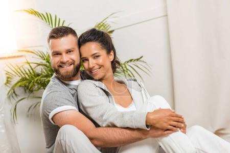 Photo pour Portrait de l'homme joyeux étreignant femme et regardant la caméra - image libre de droit