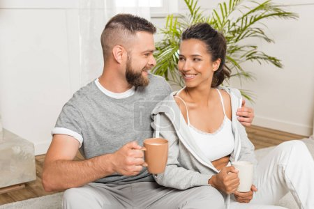 couple drinking coffee while sitting at home