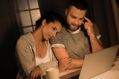 Foto de Pareja pensativo joven sentados juntos y mirando en el ordenador portátil - Imagen libre de derechos