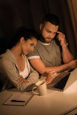 pensive couple looking at laptop at home