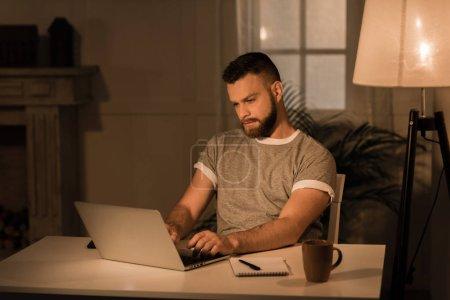 Photo pour Jeune homme cher travaillant sur ordinateur portable tout en étant assis à la maison - image libre de droit