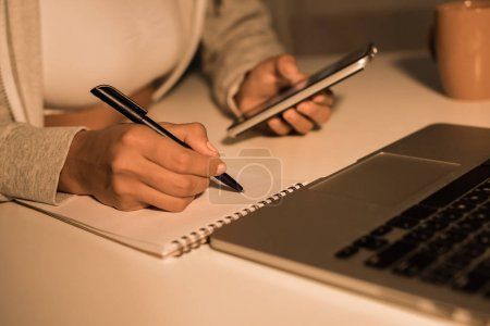 woman writing at notebook while holding smartphone