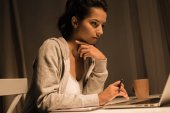 pensive woman working on laptop at home
