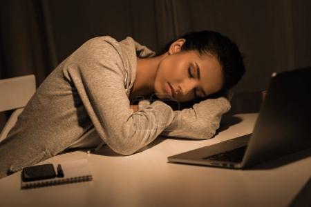 Photo pour Jeune femme fatiguée dormir à table près d'un ordinateur portable à la maison - image libre de droit