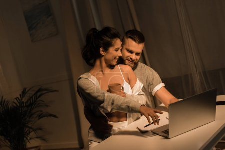 smiling couple using laptop at home