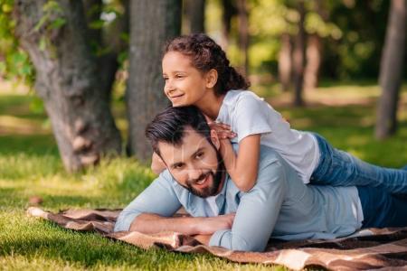 Girl lying on fathers back