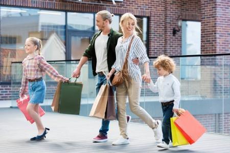 Photo pour Parents et petits enfants marchant avec des sacs à provisions dans le centre commercial - image libre de droit