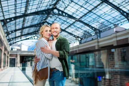 Photo for Portrait of smiling couple looking at camera hugging each other at shopping mall - Royalty Free Image