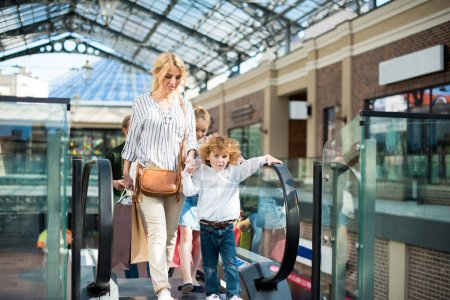 mother with kids rising on escalator in mall