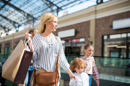 Photo pour Mère avec sac à provisions dans la main marchant dans le centre commercial avec les enfants - image libre de droit