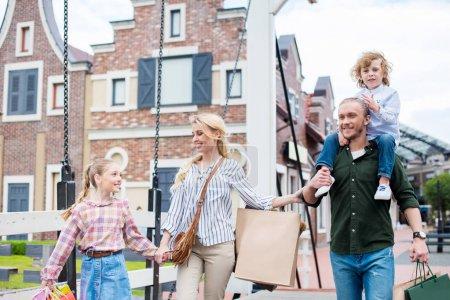 Photo pour Famille heureuse marchant ensemble et tenant des sacs à provisions sur le pont - image libre de droit