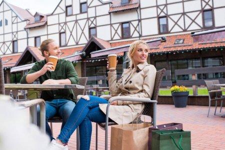Photo pour Jeune couple caucasien boire du café jetable tout en étant assis au café dans la rue - image libre de droit