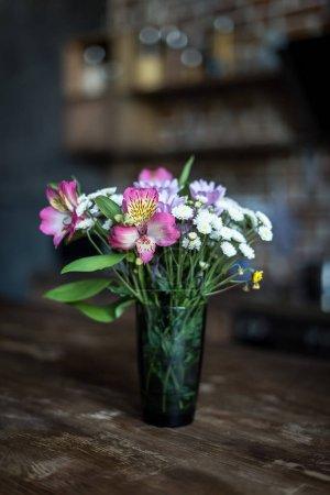 Foto de Bodegón con ramo de flores de verano a pie de florero en la mesa de madera - Imagen libre de derechos