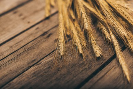 Photo for Close-up view of ripe wheat spikelets on rural wooden table - Royalty Free Image