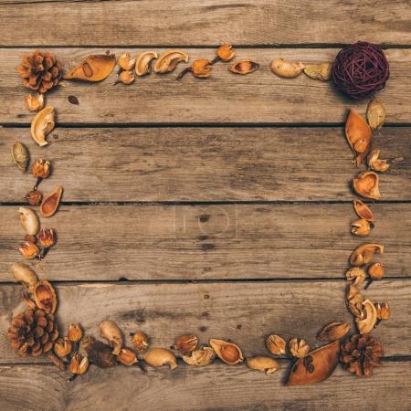 Photo pour Vue de dessus du cadre décoratif fait à partir de cônes secs, des fleurs et des graines sur une table en bois rustique - image libre de droit