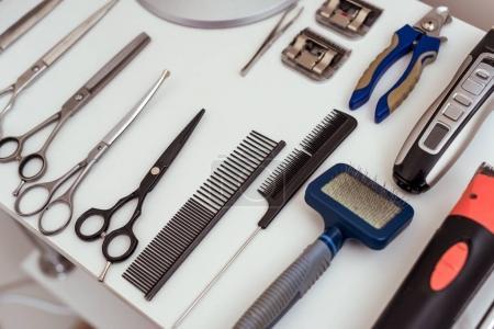 Photo pour Vue rapprochée de l'ensemble des divers outils de toilettage sur la table blanche dans le salon d'animaux de compagnie - image libre de droit