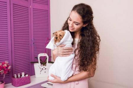 woman holding dog after bath