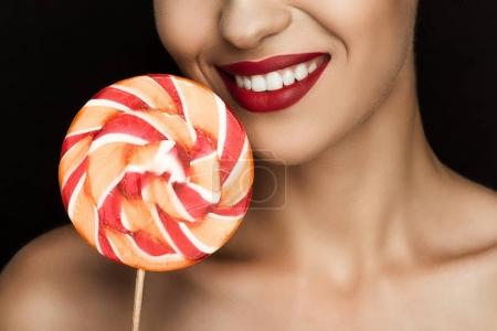Photo for Cropped view of beautiful naked woman with red lips holding lollipop, isolated on black - Royalty Free Image