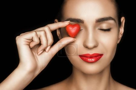 Photo for Attractive woman with closed eyes holding red heart shaped candy, isolated on black - Royalty Free Image