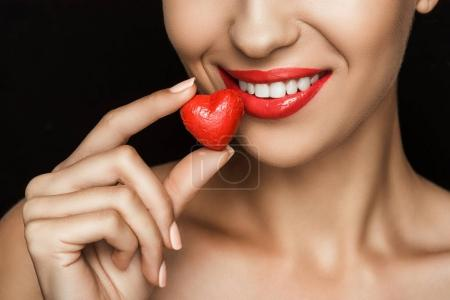 Photo for Cropped view of naked woman holding red heart shaped candy, isolated on black - Royalty Free Image