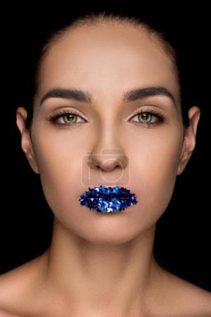 Photo pour Superbe femme à la mode avec des paillettes bleues sur les lèvres, isolées sur fond noir - image libre de droit