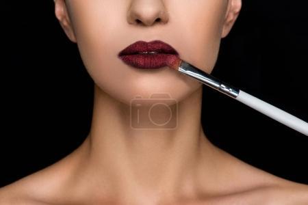 woman applying dark lipstick