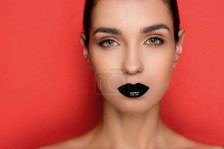 Photo pour Magnifique femme à la mode avec des lèvres noires regardant la caméra, isolé sur rouge - image libre de droit