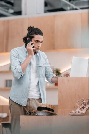 Photo pour Concentré jeune propriétaire de magasin parler sur smartphone et en utilisant un ordinateur portable à l'intérieur - image libre de droit