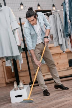man sweeping floor in boutique