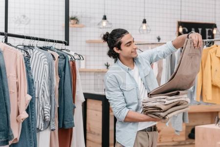 Photo pour Jeune entrepreneur détenant des tas de pantalon alors qu'il travaillait dans la boutique avant ouverture - image libre de droit