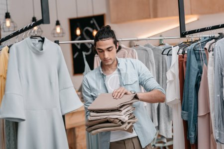 Photo for Young business owner holding pile of pants while working in boutique before opening - Royalty Free Image