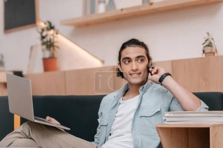 Photo for Handsome smiling young man talking on smartphone and using laptop while working - Royalty Free Image