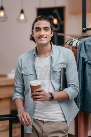 Photo pour Beau jeune homme de boire du café de gobelet en papier et souriant à la caméra - image libre de droit