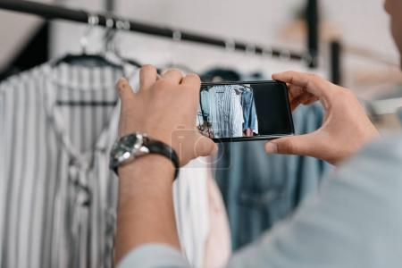man photographing clothes with smartphone