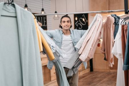 Photo for Handsome young man standing between hangers with clothes and smiling at camera in boutique - Royalty Free Image