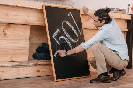 Photo pour Jeune vendeur masculin dessin cinquante pour cent signe de réduction sur tableau noir - image libre de droit