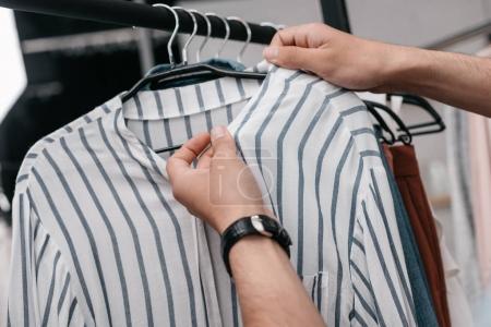 Photo pour Gros plan vue partielle du jeune homme, travaillant avec des vêtements sur cintres en magasin - image libre de droit
