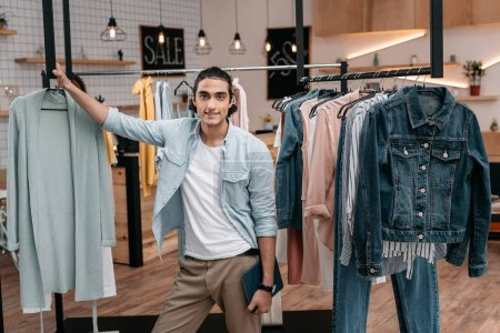 Photo for Handsome young man holding digital tablet and smiling at camera while working in boutique - Royalty Free Image