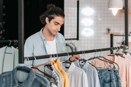 Photo pour Beau jeune propriétaire de boutique choisissant chemises sur cintres et souriant - image libre de droit