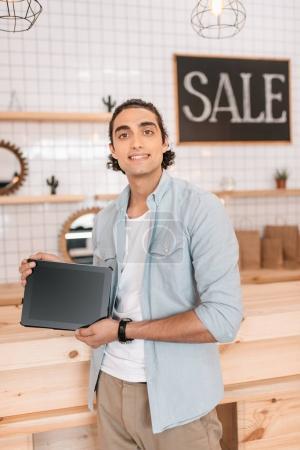 Photo pour Propriétaire de la boutique jeune beau tenant une tablette numérique avec écran blanc et souriant à la caméra - image libre de droit