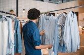 Man choosing shirts in boutique