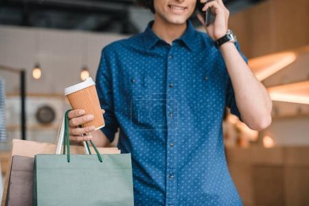 Photo pour Photo recadrée de jeune homme portant des sacs à provisions et tasse de papier tout en parlant sur smartphone - image libre de droit