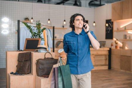 Foto de Joven sonriente con bolsas y papel mientras habla en smartphone en boutique - Imagen libre de derechos